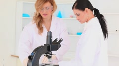Scientist women looking through a microscope Stock Footage