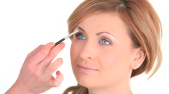 Young woman being made up by a make-up artist Stock Footage