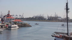 Port of Long Beach shipyard container cranes in back with schooner in foreground Stock Footage