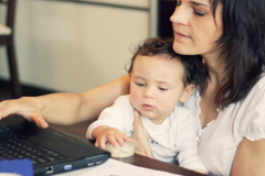 Working mother in front of the laptop holding baby and talking on cellphone Stock Footage