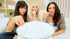 Three Girlfriends Watching Scary Movie with Popcorn Stock Footage