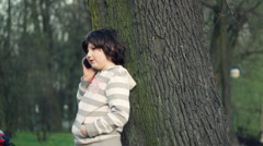Young boy standing by the tree and talking on mobile phone, outdoors HD Stock Footage