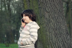 Young boy standing by the tree and talking on mobile phone, outdoors NTSC Stock Footage