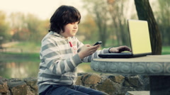 Young boy talking on mobile phone and working on laptop in the park HD Stock Footage