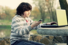 Young boy talking on mobile phone and working on laptop in the park NTSC Stock Footage