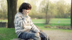 Young boy sitting in the park and talking on mobile phone, outdoors HD Stock Footage