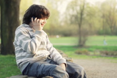 Young boy sitting in the park and talking on mobile phone, outdoors NTSC Stock Footage