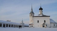 People walking in front of the traditional church covered with snow in Suzdal Stock Footage