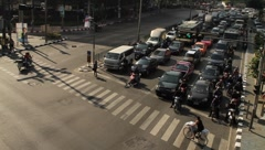 Bangkok traffic with cars and motor scooters waiting for signal on intersection Stock Footage