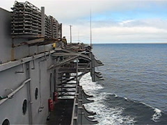 Tilt down from Navy aircraft carrier underway in the Pacific Ocean to its wake Stock Footage