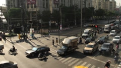 Bangkok traffic with cars and motor scooters departing from intersection Stock Footage
