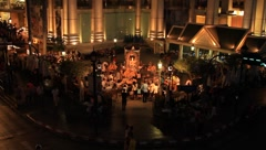 Crowded people worshipping in front of a spirit house in Bangkok at night Stock Footage