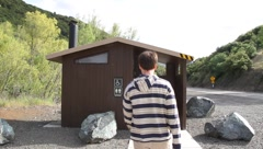Man using public park restroom Stock Footage