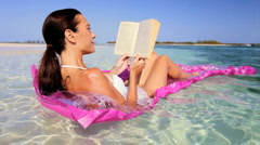 Beautiful Woman on Floating Bed with Book Stock Footage