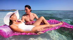 Vacation Couple in Ocean with Air Mattress Stock Footage