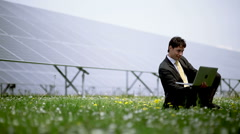 Engineer on laptop at solar power station Stock Footage