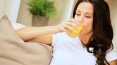Female on Home Couch Drinking Orange Juice Stock Footage