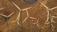 Windmill power generators truss tower structures in the foothills Stock Footage