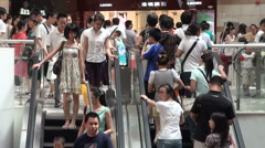 People on escalators in Guangzhou shopping mall - stock footage