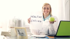 Female doctor in the office holding apple and paper sheet with HEALTHY EATING Stock Footage