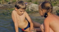 boy and girl playing in the water at the shore Footage