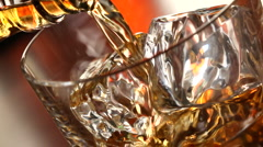 Pouring a scotch whiskey on the rocks - stock footage