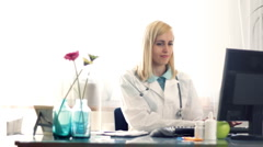 Female doctor checking working on computer and writing rx prescription HD Stock Footage