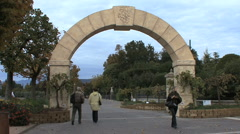 Peopl walk through an arch by a park Stock Footage