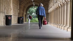 Women Walking Down Pillared Hall Stock Footage