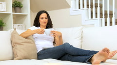 Brunette Girl on Home Couch Drinking Coffee Stock Footage