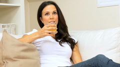 Female on Home Couch With Orange Juice Stock Footage