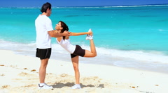 Healthy Couple Doing Muscle Stretches on Beach Stock Footage