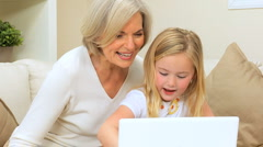 Loving Grandma with Grandchild Playing on Laptop - stock footage