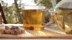 Woman mixes glass of tea outdoors - stock footage
