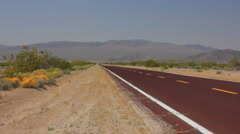 Red paved road in the Mohave desert from somewhere Stock Footage