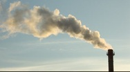 Smoke from the chimney, backlit by sun, against blue sky Stock Footage