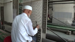 China muslim carpet making factory weaving labor man male production Stock Footage