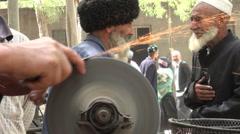 Uyghur minority China senior men old greeting friends tools sparks sharp Stock Footage