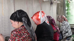 Veiled women making carpets in Xinjiang, muslim minority in China - stock footage