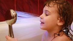 Girl play at the bathroom with led light spray Stock Footage