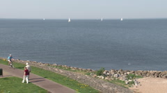 Cyclists and walkers on quay of Urk Stock Footage