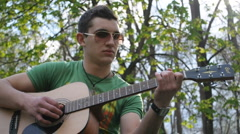 Playing guitar at the park - stock footage