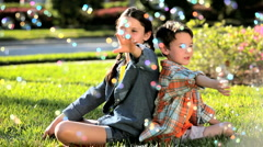 Young Children Outdoors Surrounded by Play Bubbles Stock Footage