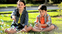 Two Children Outdoors with Play Bubbles Stock Footage