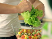 Stock Video Footage of Woman's hands shredding lettuce into a glass bowl