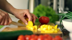 Stock Video Footage of Woman's hands cutting yellow pepper, behind fresh vegetables