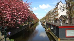 Amsterdam Holland floating house, canals, bridges, buildings, boats - stock footage
