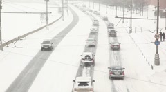 City road traffic passes alonf the river under snowfall Stock Footage