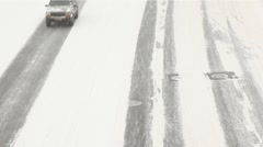 Low speed city road traffic passes by under snowfall Stock Footage