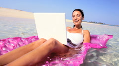 Brunette Female Floating on Air Mattress with Laptop Stock Footage